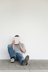 Mature man holding digital tablet in front face