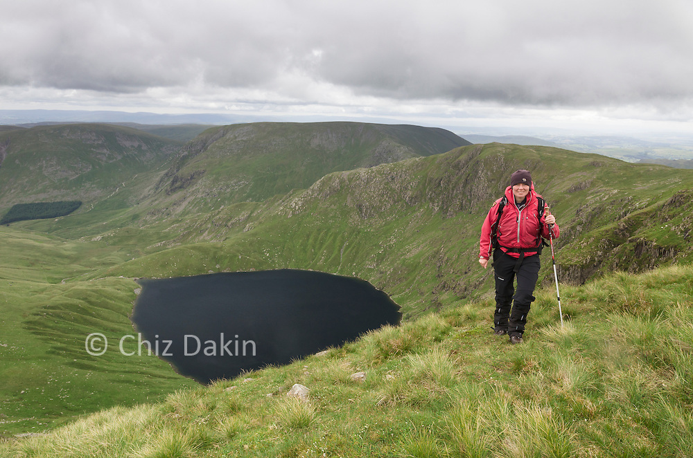 Walker above Blea Water as the ridge of Rough Crag joins High Street