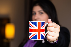 Assistant Manager Bruna Salvadori pose with a mug left in one of the hotel's rooms. London, July 24 2019.