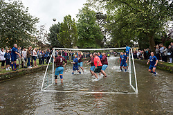 © Licensed to London News Pictures; 30/08/2021; Bourton-on-the-Water, UK. A century-old Gloucestershire tradition of five-a-side football is played in the river Windrush every August Bank Holiday, drawing hundreds of spectators. Goalposts are set up in the river and two teams from Bourton Rovers 1st XI and 2nd XI battle it out for the honours attempting to score as many goals as possible. The match ended in a draw 1-1. Local legend has it that the event began when drunken football fans spilled out of the nearby Kingsbridge Inn to play an impromptu match. Photo credit: Simon Chapman/LNP.