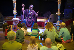 West African storyteller; Seyi Ogunjobi; on stage in front of group of children at the WOMAD (World of Music; Arts and Dance) Festival in reading; 2005,