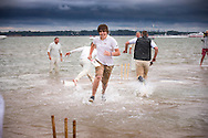 Players running between the 'wicket' during the annual Bramble Bank cricket match in the middle of the sea. The eccentric game involves members of the Royal Southern Yacht Club in Hamble playing against the Island Sailing Club from Cowes on the Brambles, a patch of sand in the Solent, only visible for a few minutes on the spring tide. The teams take turns in winning. This year the Royal Southern team won and hosted dinner at their club house.<br /> Picture date Monday 31st August, 2015.<br /> Picture by Christopher Ison. Contact +447544 044177 chris@christopherison.com