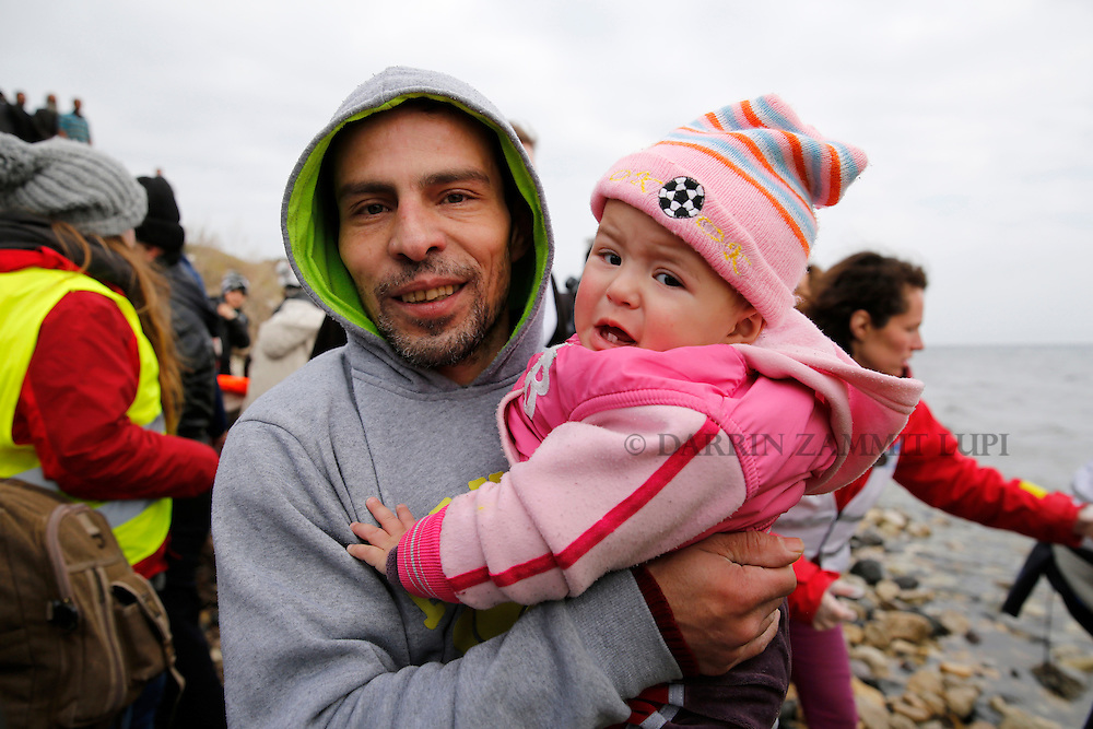 A migrant carries his baby after arriving on a rubber dinghy packed with refugees and migrants on a beach on the Greek island of Lesbos, January 29, 2016. Photo: Darrin Zammit Lupi