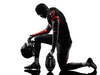 one american football player kneeling in silhouette shadow on white background