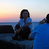 Central America, Cuba, Havana. Couple taking sunset pictures on the Malecon.