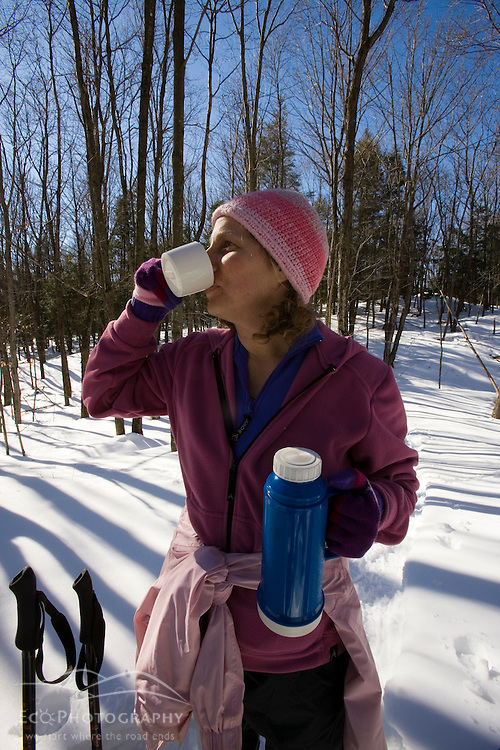 A woman drinks hot chocolate on the Cross-Rivendell Trail in West Fairlee, Vermont.  Bald Top Mountain.  Winter.