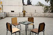A kitchen hand in the the Indian Coffee House looks over the wall for monkeys, Baba Kharak Singh Marg, New Delhi.<br /> The Coffee House dates back almost fifty years, first in central Connaught Place, then Janpath and now at the top of a rather shabby shopping centre. Still run by the Indian Coffee Workers Cooperative Society, it was a regular haunt for politicos in Delhi and It's clientelle is still well read and intellectual.