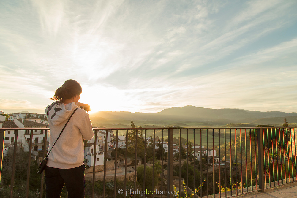 Tourists looking at view at sunrise, Ronda, Andalusia, Spain