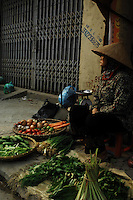 The day comes to a close for a woman selling vegetables in Hanoi, Vietnam.  (Laura Fong Torchia/Special to the Akron Beacon Journal)
