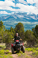 Man riding all terrain vehicle (with Sneffels Range in background), RIdgway, Colorado USA