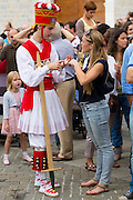 Dancer in costume chats with woman in casuals at San Fermin Fiesta at Pamplona, Navarre, Northern Spain
