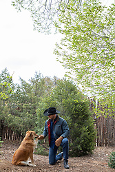 cowboy enjoying time with a Golden Lab dog outdoors