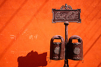 Decorative litter containers advertising CocaCola against an orange adobe wall, Mexico