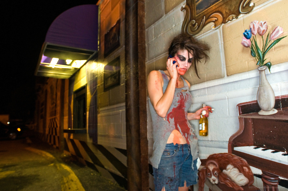 Audrey Whelan talks on the phone outside Old Town Liquors while waiting for friends after the 8th Annual Louisville Zombie Walk, Wednesday, Aug. 29, 2012 in Louisville, Ky. (Photo by Brian Bohannon)