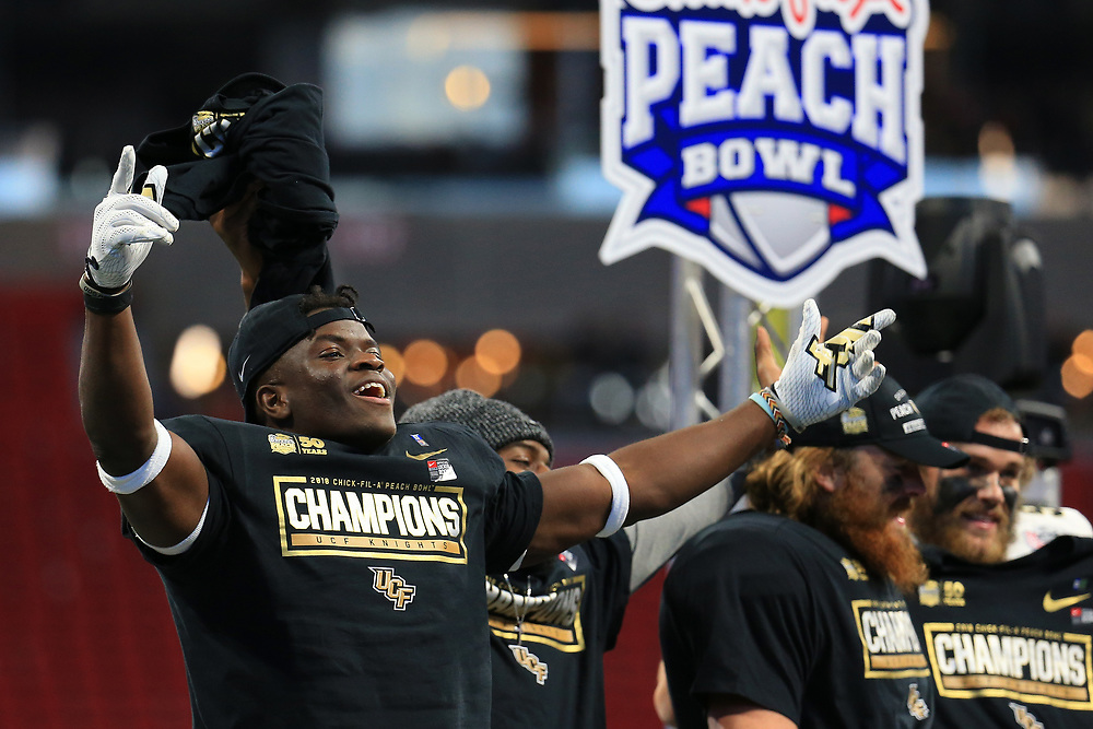 UCF Knights players celebrate beating the Auburn Tigers during the 2018 Chick-fil-A Peach Bowl NCAA football game on Monday, January 1, 2018 in Atlanta. (Daniel Shirey / Abell Images for the Chick-fil-A Peach Bowl)