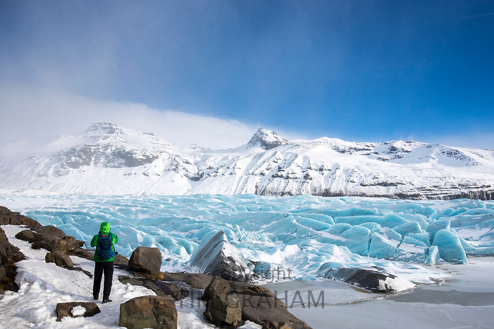 Tourist photographs glacial tongue of Svinafellsjokull glacier an outlet glacier of Vatnajokull, largest ice cap in Europe, South Iceland