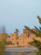 A kasbah sits on the banks of a dried up river in the Skoura Oasis in Morocco