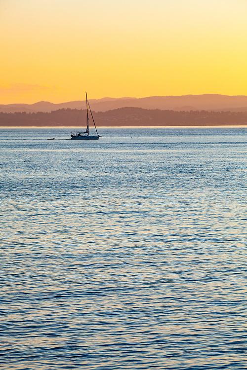 A sailboat motoring through the haro Strait between San Juan Island and Vancouver Island.