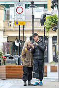 A young couple is seen entertaining themselves with a photo camera near Covent Garden underground station in central London on Monday, May 11, 2020. <br />