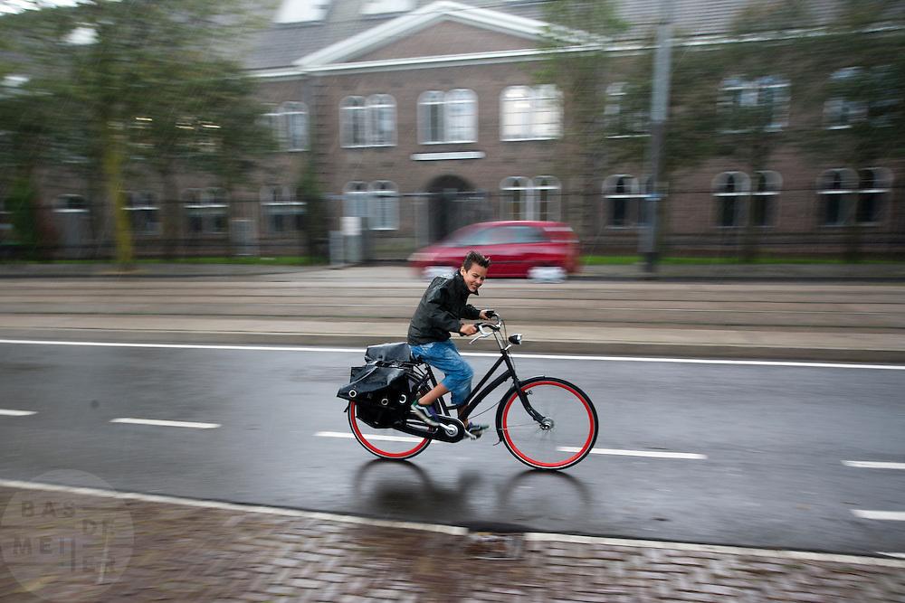 Een jongen fietst in de regen door de Sarphatistraat in Amsterdam.<br /> <br /> A boy is cycling in the rain at the Sarphatistraat in Amsterdam