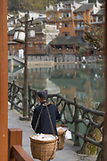 Rear view of a senior man carrying baskets in an ancient Chinese town, Fenghuang, Hunan Province, China