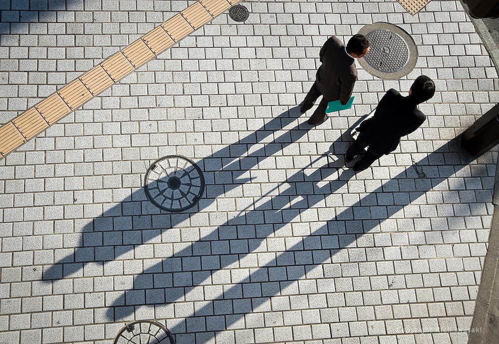 Overhead view of businessmen and shadows on sidewalk near the Ginza street crossing, Kumamoto city, Kumamoto Prefecture, Japan