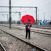 A refugee boy carrying rain coats walks on the rail line in the refugee transit camp of Idomeni, Greece. <br /> <br /> Thousands of refugees are stranded in Idomeni unable to cross the border. The facilities here are stretched to the limit and the conditions are appalling. It's raining, it's cold there is mud everywhere and there is no hope that the border will open anytime soon.