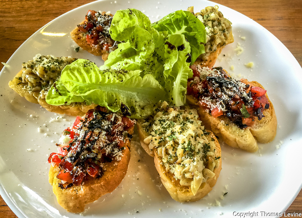 6 small toasted appetizer brochettes on a white plate and wood table. Green lettuce in the middle.