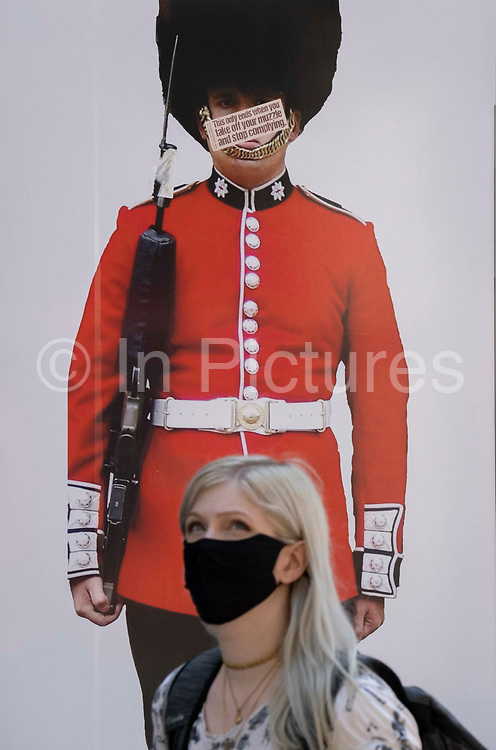 A masked shopper walks beneath the image of a guardsman whose face has been obscured by an anti-vaxx message mocking pandemic face coverings, on Covid Freedom Day. This date is what Prime Minister Boris Johnsons UK government has set as the end of strict Covid pandemic social distancing conditions with the end of mandatory face coverings in shops and public transport, on 19th July 2021, in London, England.