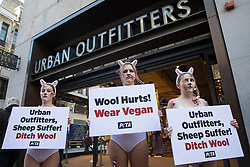 London, UK. 21st October, 2021. PETA supporters dressed as bloodied sheep protest outside a branch of Urban Outfitters in Oxford Street to call for an end to wool sales. The protest forms part of an international PETA campaign to urge Urban Outfitters Inc brands including Anthropologie and Free People to stop selling materials cruelly taken from animals.