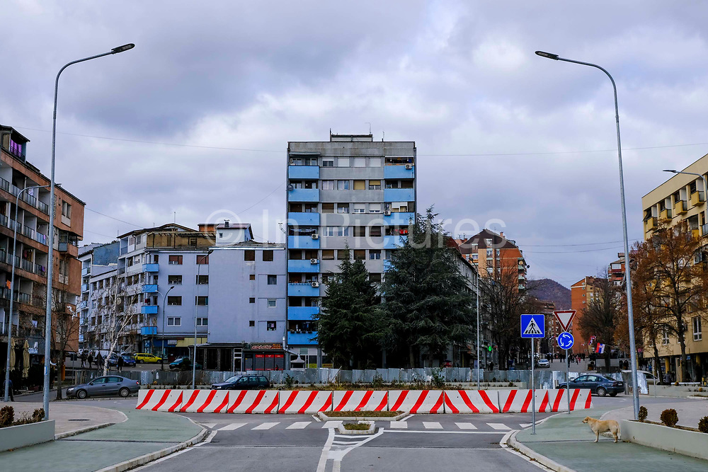 A view from Mitrovic bridge looking north into the Serbian side of town at the makeshift boarder fence which separates the Serbian and Albanian districts of Mitrovica, Kosovo on the 12th of December 2018. The bridge was rebuilt with funding from the EU. Mitrovica or Kosovska Mitrovica is a city and municipality located in Kosovo. Settled on the banks of Ibar and Sitnica rivers, the city is the administrative center of the Mitrovica District.