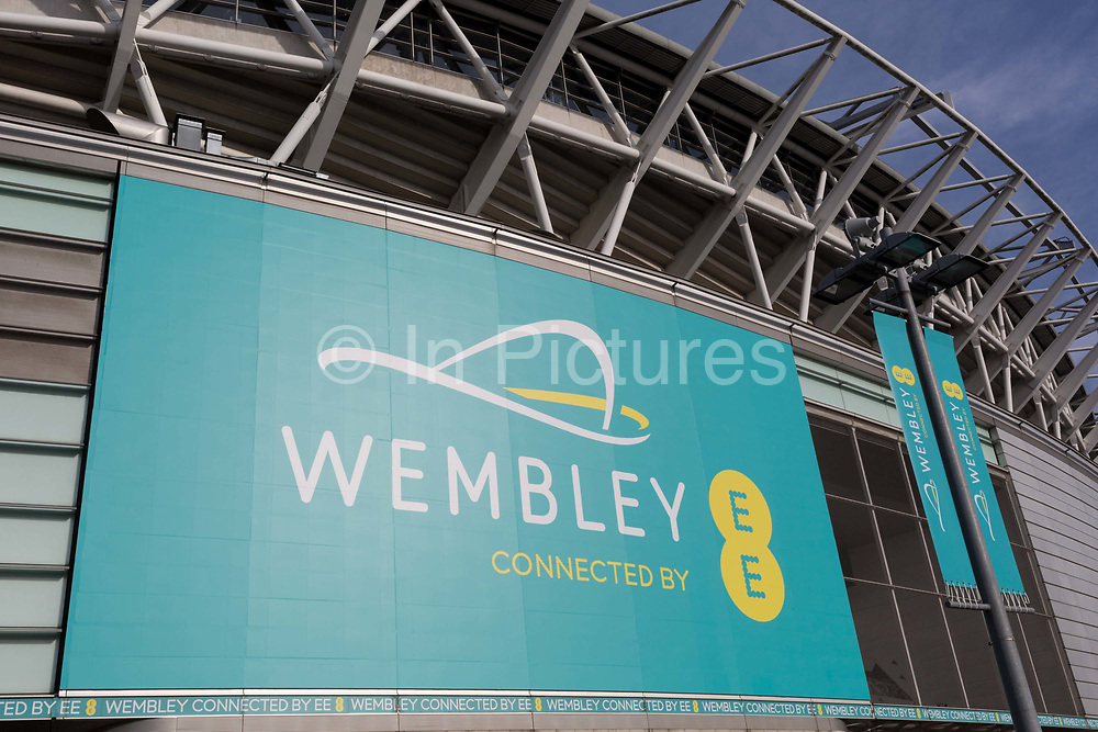 A banner for Wembley Stadium and the communications brand EE, on 6th November 2019, in Wembley, London, England. Wembley Stadiums mobile app and an interactive LED lighting system on the arch, which can respond to goals scored, crowd noise plus trialling contactless payments and ticketing with an aim to make over 50% of payments contactless. In 2018, the world's first live sporting event to be broadcast over 5G used remote production.