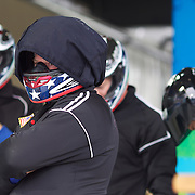 """A USA team prepare themselves in the start area during the Bobsleigh Four-man competition  at The Whistler Sliding Centre, Whistler, during the Vancouver Winter Olympics. 26th February 2010. Photo Tim Clayton..'BOB'..Images from the Four-man Bobsleigh Competition. Winter Olympics, Vancouver 2010..History was made at the Whistler Sliding Centre when the USA four-man bobsleigh team, led by Steven Holcomb took the Gold. The first time since 1948, a gap of 62 years, since the USA have won an Olympic Bobsleigh gold and they did it with their sleigh named """"Night Train""""...The four days of practice and competition show the tension, nervousness and preparation as the teams of hardened men cope with the challenge of traveling at average speeds of over 150 km an hour. Indeed, five teams had already pulled out of the event before the opening heats because of track complexity, speed and fear, and on the final day, another four teams did not start after six crashes in the first two heats...Teams warm up behind the start complex, warming muscles in the cold in preparation for the explosive start. Many teams prepare in silence, mentally preparing themselves as they wait at the top of the run, in the bobsleigh sheds and the loading areas for their turn. When it's time to slide each team performs it's own starting ritual, followed by the much practiced start out of the blocks for just over four seconds, the teams are then in the hands of the accomplished drivers as they hurtle down the track for just over fifty seconds...Spectators clamber for the best position on track to see the sleighs for a split second, many unsuccessfully try to capture the moments on camera, The rumble of the sleigh is heard then the crowds gasp as it hurtles past in a blur...The American foursome of  Steven Holcomb, Justin Olsen, Steve Mesler and Curtis Tomasevicz finished with a pooled four-heat time of 3min 24.46sec. The German team led by Andre Lange won the Silver Medal in a combined time of 3min 24.84sec"""