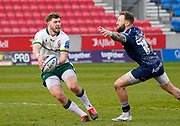 Sale Sharks wing Byron McGuigan tries to block a pass from London Irish Centre Theo Brophy-Clews during a Gallagher Premiership Round 14 Rugby Union match, Sunday, Mar 21, 2021, in Eccles, United Kingdom. (Steve Flynn/Image of Sport)