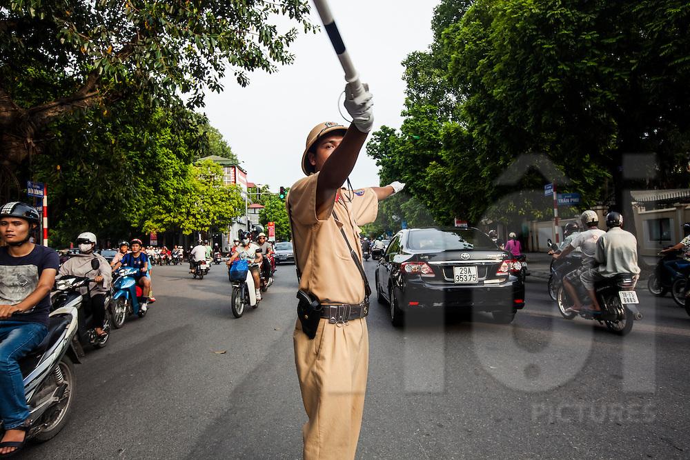 A policeman regulates traffic at a crossroad of Hanoi, Vietnam, Southeast Asia