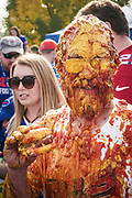 """SHOT 10/22/17 9:40:07 AM - The ketchup and mustard shower while tailgating at the Hammer's Lot at the Pinto Ron tailgate party before the Buffalo Bills faced the Tampa Bay Buccaneers in Orchard Park, N.Y. Ken Johnson, better known as """"Pinto Ron"""", (born 1958) is a Buffalo Bills fan known for attending every single Bills home and away game and hosting a tailgate party since 1994. He is known for his red Ford Pinto and antics cooking food on his car hood in a variety of objects such as a shovel and army helmet; furthermore, he holds a tradition of being doused in ketchup and mustard. Most notably he served shots out of a bowling ball until he was forced to shut down by the National Football League (NFL) Johnson moved his tailgate party to private property next to the stadium where the NFL has no jurisdiction and was able to resume serving bowling ball shots. He has been featured in multiple NFL Films, as well as the made-for-TV movie Second String. (Photo by Marc Piscotty / © 2017)"""
