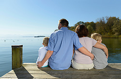 Family sitting and embracing each other on boardwalk, Bavaria, Germany