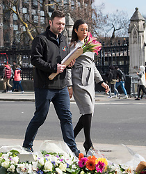 © Licensed to London News Pictures. 22/03/2018. London, UK. A man and woman place flowers on Parliament Square, outside the Houses of Parliament in Westminster, London on the one year anniversary of the Westminster Bridge Terror attack in which lone terrorist killed 5 people and injured several more, in an attack using a car and a knife. The attacker, 52-year-old Briton Khalid Masood, managed to gain entry to the grounds of the Houses of Parliament and killed police officer Keith Palmer. Photo credit: Ben Cawthra/LNP