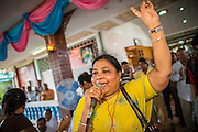 """29 SEPTEMBER 2012 - NAKORN NAYOK, THAILAND:  A woman sings praise and seeks the blessings of Ganesh during observances of Ganesh Ustav at Wat Utthayan Ganesh, a temple dedicated to Ganesh in Nakorn Nayok, about three hours from Bangkok. Many Thai Buddhists incorporate Hindu elements, including worship of Ganesh into their spiritual life. Ganesha Chaturthi also known as Vinayaka Chaturthi, is the Hindu festival celebrated on the day of the re-birth of Lord Ganesha, the son of Shiva and Parvati. The festival, also known as Ganeshotsav (""""festival of Ganesha"""") is observed in the Hindu calendar month of Bhaadrapada, starting on the the fourth day of the waxing moon. The festival lasts for 10 days, ending on the fourteenth day of the waxing moon. Outside India, it is celebrated widely in Nepal and by Hindus in the United States, Canada, Mauritius, Singapore, Thailand, Cambodia, Burma , Fiji and Trinidad & Tobago.     PHOTO BY JACK KURTZ"""