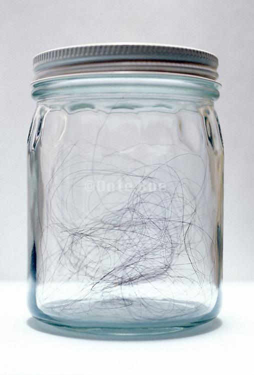 Long black hair in a glass jar.