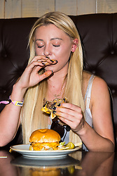 DAILYSTAR - Professional food challenger and social media personality Kate Ovens, XX, from London demolishes two 14 ounce burgers at the Handmade Burger Co in Wembley in a time of 8 minutes and 40 seconds - 18 seconds per ounce. London, April 17 2018.
