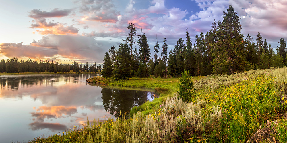 A beautiful Summer sunrise on the banks of the calm waters of the Henry's Fork River in Idaho.