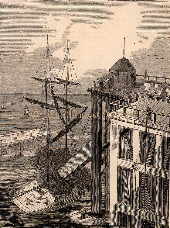Seaham Harbour, County Durham, England. Loading a sailing vessel with coal. The railway wagons were unloaded into the top of the 'spout' on the staithe or wharf. The bottom of the spout was positioned over the hold of the ship. Seaham Harbour and New Town were founded in 1828 to export coal from the east of the Durham Coalfield.  Engraving from 'The Penny Magazine' (London, April 1835).