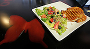 A butterfly pattern is painted into each of the tabletops of the Butterfly Patio's dining area. The house salad has strawberries, blueberries, praline pecans and a raspberry-walnut-lime-poppy seed vinaigrette. At right is a goumet panini sandwich.