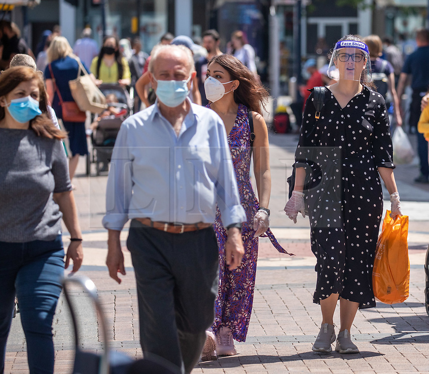 © Licensed to London News Pictures. 15/06/2020. London, UK. Shoppers in Kingston, South West London wearing protective visors and gloves as non essential shops are given the green light to open in England after 3 months of being closed due to the coronavirus pandemic. Also commuters are told to wear face masks from Monday while travelling on Public transport. Photo credit: Alex Lentati/LNP