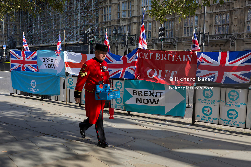On the day that the EU in Brussels agreed in principle to extend Brexit until 31st January 2020 (aka 'Flextension') and not 31st October 2019, a Chelsea Pensioner selling Remembrance poppies, walks past Brexit Party flags and banners during a Brexit protest outside parliament, on 28th October 2019, in Westminster, London, England.
