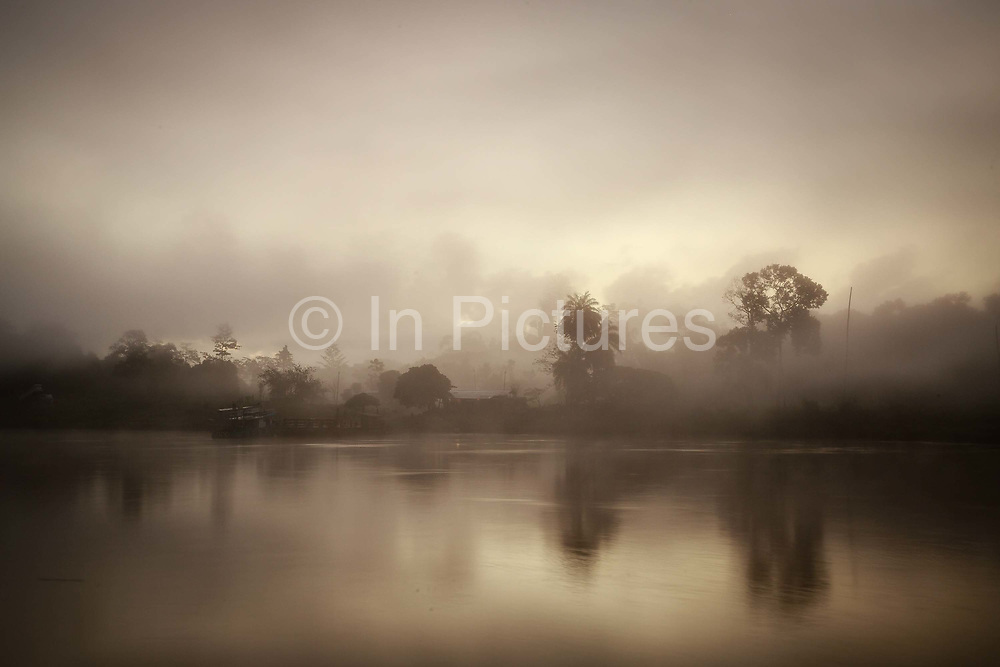 The sun rises through low cloud on the Kinabatangan River, within the Kinabatangan Wildlife Sanctuary, in Sukau, Sabah, Malaysia.