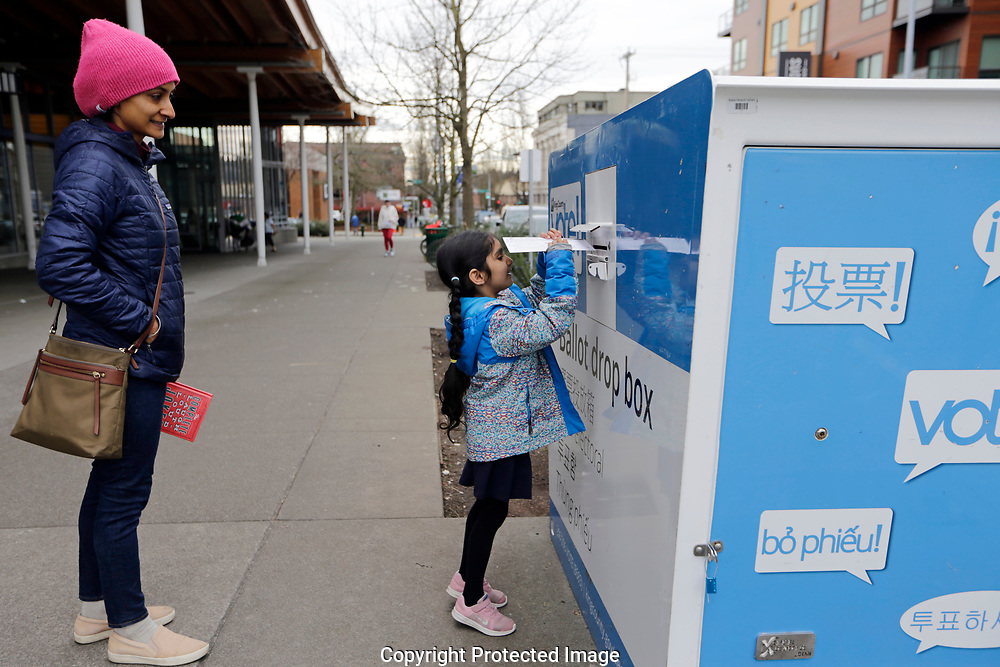 Gagan Thind  watches as her daughter Seva drops off ballots in the Washington State primary, Tuesday, March 10, 2020 in Seattle. Washington is a vote by mail state. (AP Photo/John Froschauer)