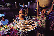 An Indonesian woman holds a tray of honeycomb containing bee larvae. The honeycomb is an expensive and sought after commodity; it is boiled to release the bee larvae, which are then cooked with coconut oil, garlic, onion, chiles, lemon, fermented fish, sliced green papaya, long beans, and greens, Ubud, Bali, Indonesia. (Man Eating Bugs page 63)