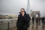 A man on his mobile phone crossing London Bridge in the rain and high winds.